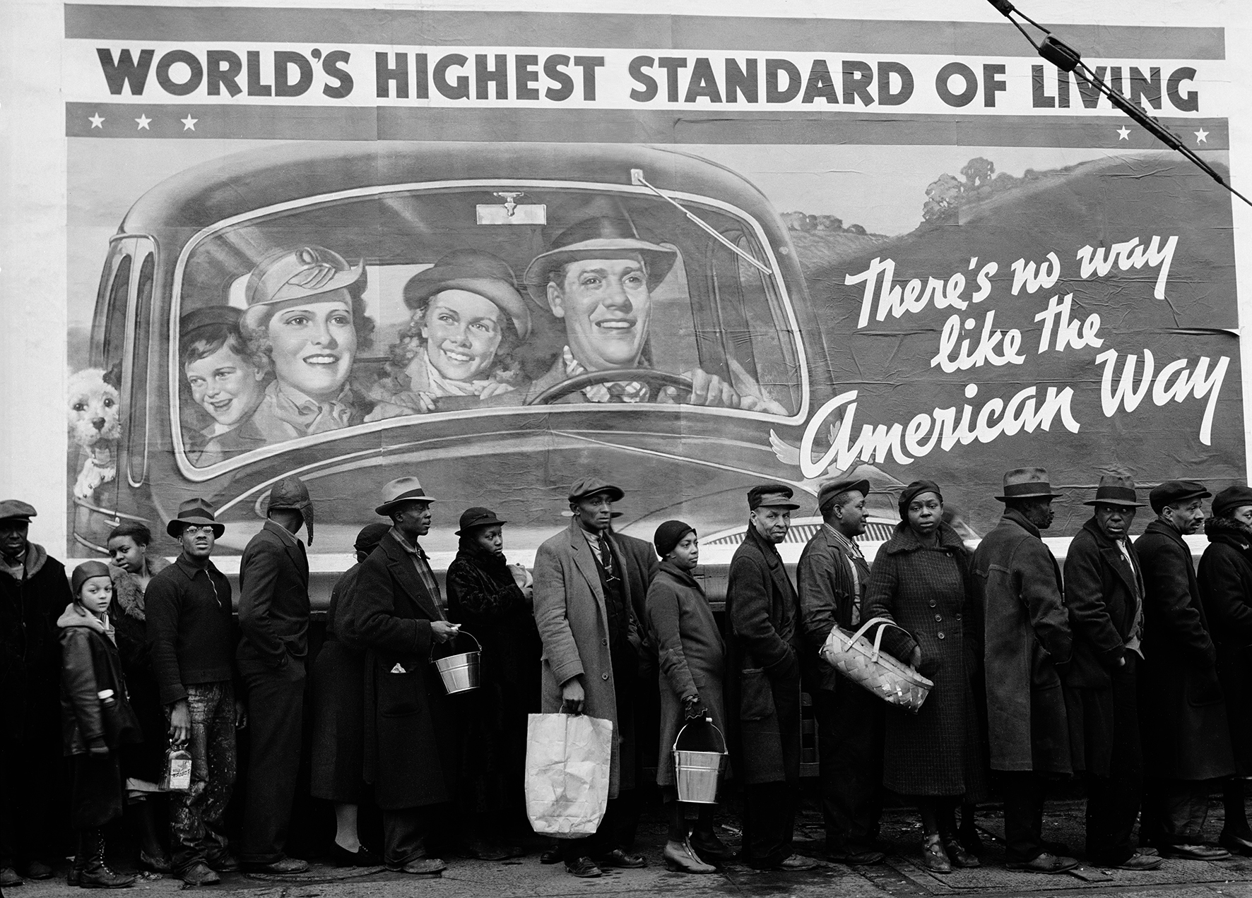 UNITED STATES - CIRCA 1937:  African American flood victims lining up to get food and clothing from a relief station in front of a billboard ironically proclaming WORLD'S HIGHEST STANDARD OF LIVING/THERE'S NO WAY LIKE THE AMERICAN WAY.  (Photo by Margaret Bourke-White/Time & Life Pictures/Getty Images)