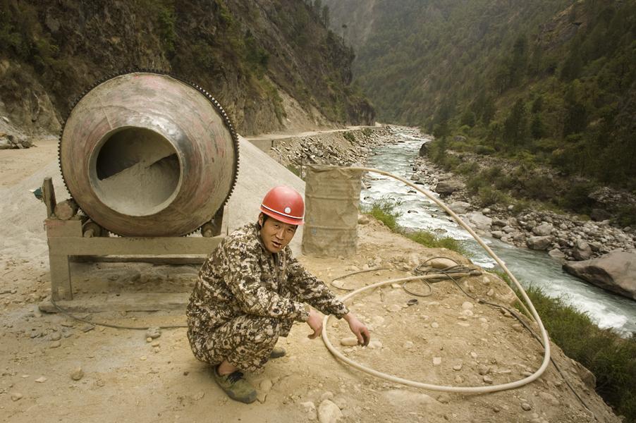 Operaio cinese a lavoro lungo il percorso della nuova autostrada