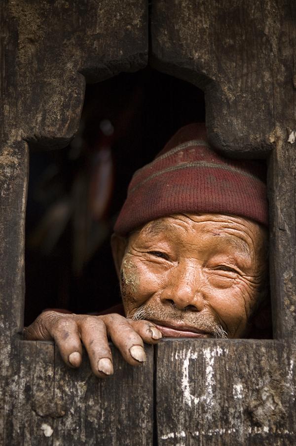 Profugo tamang affacciato alla finestra di casa sua nel villaggio di Gatlang.