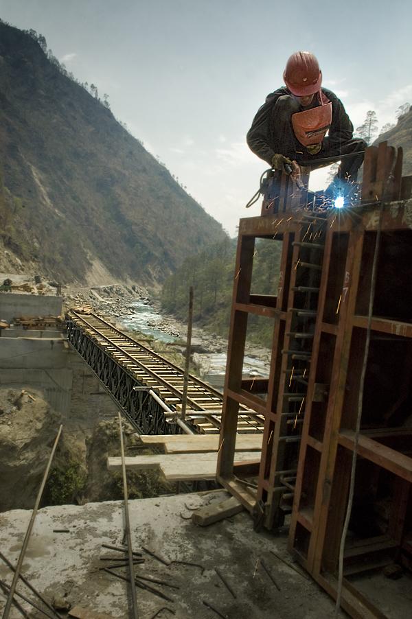 Un operaio cinese salda lo scheletro dell'autostrada