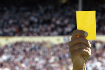 Hand holding up a yellow card