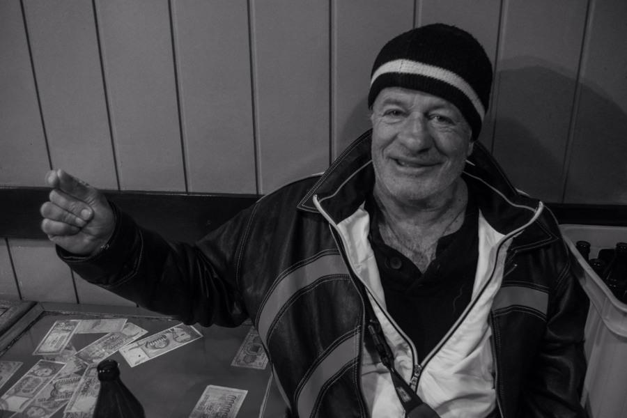 Dzeilan sorrifente seduto al tavolino, su cui si vedono alcune banconote e la bottiglia di birra